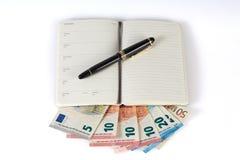 Stift und Buch lokalisiert auf europäischen Banknoten Stockfoto