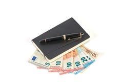 Stift und Buch lokalisiert auf europäischen Banknoten Stockbild