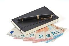 Stift und Buch lokalisiert auf europäischen Banknoten Lizenzfreie Stockfotos