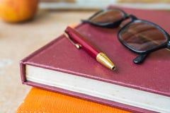 Stift und Gläser auf Büchern Stockbild