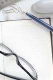 Stift und Gläser auf dem offenen Notizbuch Stockfotografie