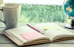 Stift und klebrige Anmerkung über offenes Notizbuch auf Kaffeetasse und Kugel Stockfoto