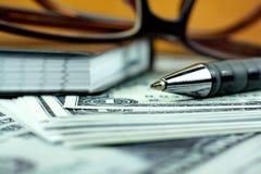 Stift und kleines Notizbuch auf US-Dollar Banknote Stockfotografie