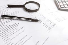 Stift und Lupe auf Finanzberichten Lizenzfreie Stockfotos