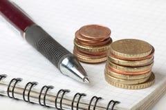 Stift und Münzen Stockbild