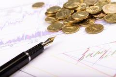 Stift und Münzen auf dem Hintergrund von Diagrammen und von Diagrammen Stockfotos