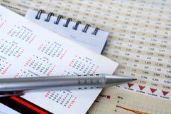 Stift und Notizblock auf Kalender Stockfotografie