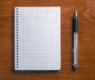 Stift und Notizbuch auf einer hölzernen Tabelle. Lizenzfreies Stockfoto