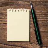 Stift und Notizbuch auf hölzerner Tabelle Lizenzfreies Stockfoto
