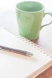 Stift und Notizbuch mit grünem Becher Stockfotos