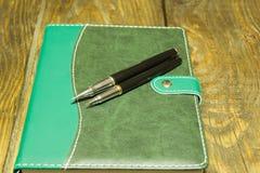 Stift und Notizbuch schließen oben auf einem rustikalen hölzernen Schreibtisch Ein strukturierter Hintergrund Kopieren Sie Pasten Stockfotografie