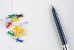 Stift und Reißzwecke auf dem Weißbuch Stockfotos