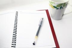 Stift und Tasse Kaffee und Notizbuch stockfotos