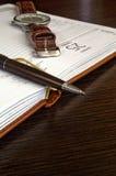 Stift und Uhr nah oben auf einem offenen Notizbuch Lizenzfreies Stockfoto