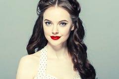 Stift upp kvinnaståenden Härlig retro kvinnlig i prickklänning med röda kanter royaltyfri bild