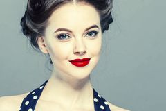 Stift upp kvinnaståenden Härlig retro kvinnlig i prickklänning med röda kanter royaltyfri fotografi