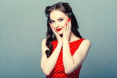 Stift upp kvinnaståenden Härlig retro kvinnlig i prickklänning med röda kanter royaltyfria bilder