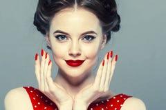 Stift upp kvinnaståenden Härlig retro kvinnlig i prickklänning med röda kanter royaltyfria foton