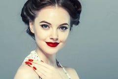 Stift upp kvinnaståenden Härlig retro kvinnlig i prickklänning med röda kanter arkivfoton