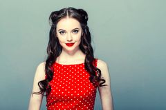 Stift upp kvinnaståenden Härlig retro kvinnlig i prickklänning med röda kanter arkivbilder