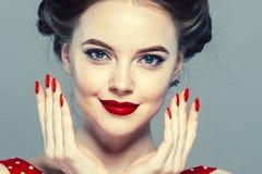 Stift upp kvinnaståenden Härlig retro kvinnlig i prickklänning med röda kanter arkivbild