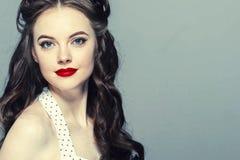 Stift upp kvinnaståenden Härlig retro kvinnlig i prickklänning med röda kanter royaltyfri foto