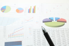 Stift vor Papieren mit Zahlen und Diagrammen Stockfoto