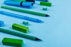 Stifte, Bleistifte, Markierungen und anderes Briefpapier, Plan auf einem blauen Hintergrund Stockfotos