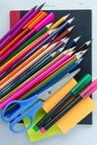 Stifte, Bleistifte, Scheren und Post-Itanmerkungen über schwarzes Anmerkungsbuch Stockfotos