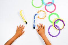 Stifte des Drucken 3d mit Fäden und den Kinderhänden Beschneidungspfad eingeschlossen Stockbild