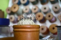 Stifte mit einem runden Hut in einem hölzernen runden Kasten auf dem Hintergrund von verschiedenen Faden lizenzfreies stockfoto