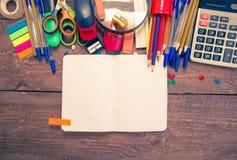 Stifte, Notizbuch, Vergrößerungsglas, Taschenrechner und Bleistifte lizenzfreie stockfotos