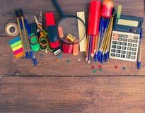 Stifte, Notizbuch, Vergrößerungsglas, Taschenrechner und Bleistifte Stockfotografie