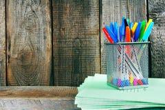 Stifte und Schreibenbücher auf einem hölzernen Regal Lizenzfreies Stockbild