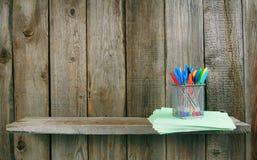 Stifte und Schreibenbücher auf einem hölzernen Regal Stockfoto
