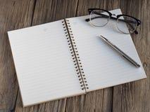 Stiftnotizbuch und -gläser auf Holz Lizenzfreie Stockfotos