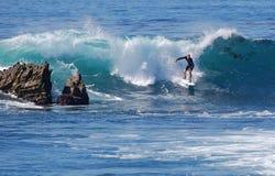 Stiga ombord surfaren som rider en våg på Laguna Beach, CA Arkivbild