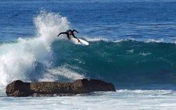 Stiga ombord surfareridningen i en våg på Laguna Beach, CA Arkivbilder