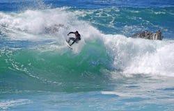 Stiga ombord surfareridningen i en våg på Laguna Beach, CA Arkivfoton