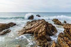 Stigande bränning som bryter på den steniga Kalifornien kusten Royaltyfria Bilder
