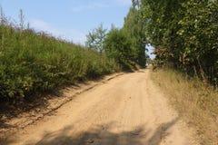 Stigande lantlig väg längs kanten av skogen Royaltyfri Fotografi