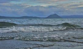 Stigande vatten på Taal sjön med den Taal vulkan som bakgrunden fotografering för bildbyråer