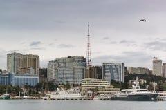 Stiger bostads- byggnader för höghus ovanför hamnstadvattenområdet på en molnig vårafton Royaltyfri Foto