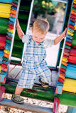 Stiger ned litet barnpojken på lekplatsen Arkivfoton