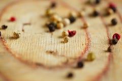 Stiger ombord blandad peppar för makroen, rosa färg, svarten, vit, gräsplan på trä Arkivbilder