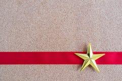 Stiger ombord den guld- stjärnan för jul och det röda bandet på kork Arkivbild