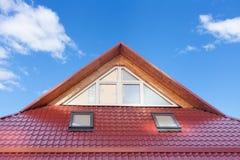 Stiger ombord det röd metall belade med tegel taket med nya vindskupefönster, taket Windows, takfönster och takskydd från snö Arkivfoto