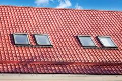 Stiger ombord det röd metall belade med tegel taket med nya vindskupefönster, taket Windows, takfönster och takskydd från snö Royaltyfri Foto