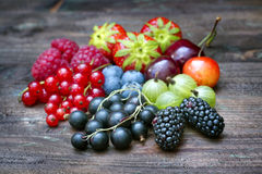 Stiger ombord lösa bärfrukter för sommar på tappning stilleben arkivfoto
