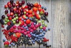 Stiger ombord lösa bärfrukter för sommar på tappning stilleben royaltyfri bild